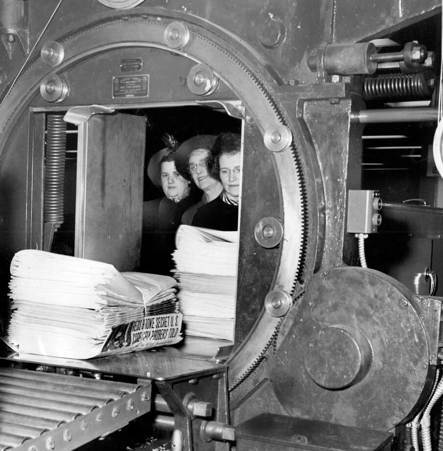 In this picture from Jan. 13, 1949, Mrs. E.G. Weatherman, Mrs. H.R. McEwen, and Mrs. De Rose Gibson watch the P-I wire type machine wrap and fasten piles of newspapers. The space that is shown in this picture is now part of the headquarters for City University of Seattle. Photo: Seattlepi.com