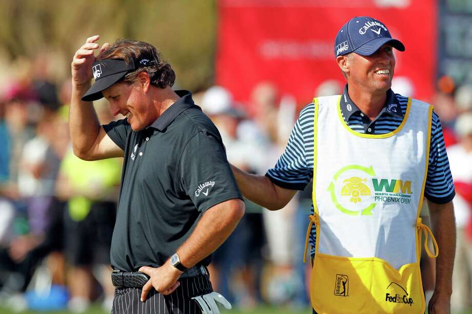 SCOTTSDALE, AZ - JANUARY 31: Phil Mickelson is consoled by his caddie Jim Mackay after missing his birdie putt on the ninth hole that would have given him a round of 59 during the first round of the Waste Management Phoenix Open at TPC Scottsdale on January 31, 2013 in Scottsdale, Arizona. (Photo by Hunter Martin/Getty Images) Photo: Hunter Martin