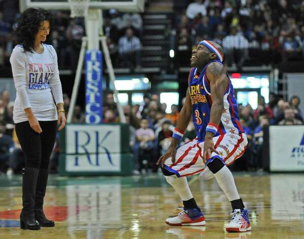 "Harlem Globetrotter ""Firefly,"", aka Siena graduate Tay Fisher, entertains the crowd, while Danielle Sommer of Rotterdam laughs at center court at the Times Union Center during a game on Sunday Feb. 5, 2012 in Albany, NY.  Sommer was brought onto the court by another Globetrotter after he borrowed her pocketbook and brought it onto the court during the game.   (Philip Kamrass / Times Union ) Photo: Philip Kamrass / 00016336A"