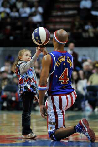 "Harlem Globetrotter player ""Flight Time"" entertains the crowd while teaching Grace Riley, 5, how to balance a spinning ball on her finger at center court at the Times Union Center during a game on Sunday Feb. 5, 2012 in Albany, NY.    (Philip Kamrass / Times Union ) Photo: Philip Kamrass / 00016336A"