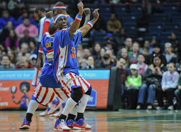 "Harlem Globetrotter ""Firefly,"", aka Siena graduate Tay Fisher, dances  on the floor of the Times Union Center during a game on Sunday Feb. 5, 2012 in Albany, NY.    (Philip Kamrass / Times Union ) Photo: Philip Kamrass / 00016336A"