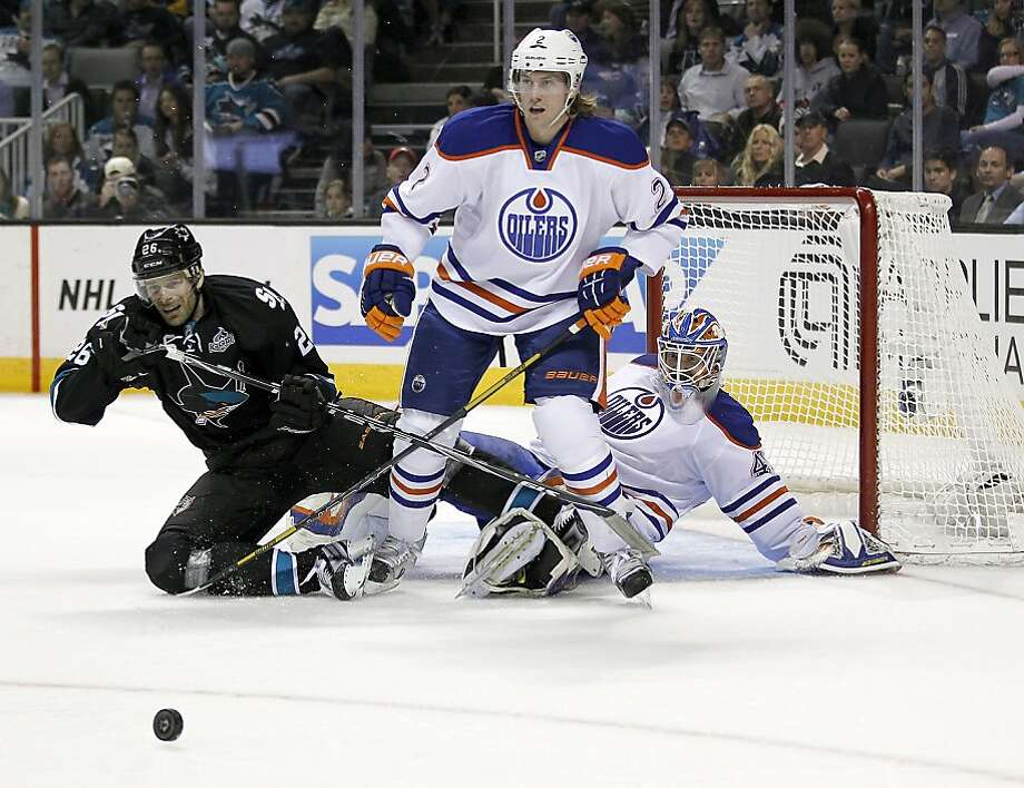 San Jose Sharks center Michal Handzus (26), of the Czech Republic, collides with Edmonton Oilers goalie Devan Dubnyk (40) as Edmonton Oilers defenseman Jeff Petry (2) looks on during the first period of an NHL hockey game in San Jose, Calif., Thursday, Jan. 31, 2013. (AP Photo/Tony Avelar) Photo: Tony Avelar, Associated Press