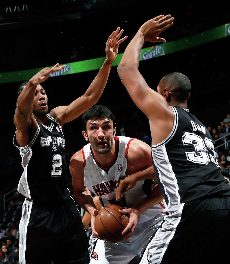 Zaza Pachulia (27) of the Hawks drives between Kawhi Leonard (2) and Boris Diaw (33) of the Spurs at Philips Arena on Jan. 19, 2013 in Atlanta. Photo: Kevin C. Cox, Getty Images / 2013 Getty Images
