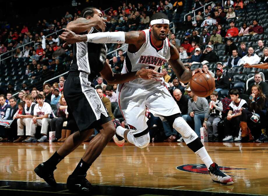 Josh Smith (5) of the Hawks drives around Kawhi Leonard (2) of the Spurs at Philips Arena on Jan. 19, 2013 in Atlanta. Photo: Kevin C. Cox, Getty Images / 2013 Getty Images