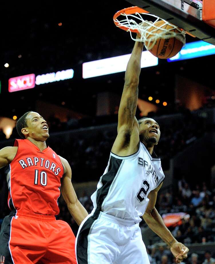 Kawhi Leonard (2) of the Spurs dunks as DeMar DeRozan of the Raptors watches during second-half action at the AT&T Center on Wednesday, Dec. 26, 2012. Photo: Billy Calzada, San Antonio Express-News / SAN ANTONIO EXPRESS-NEWS