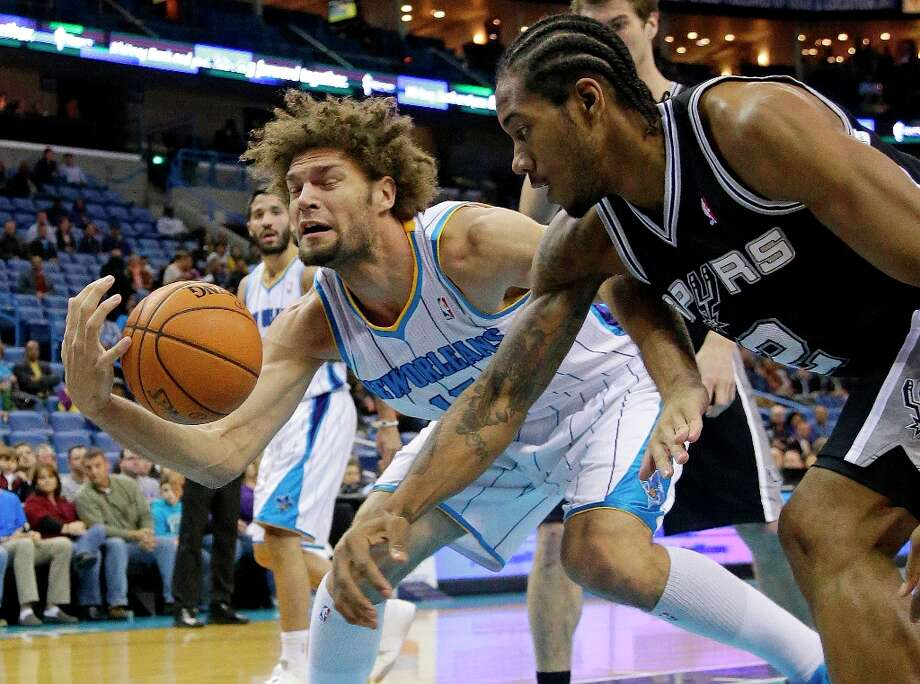 Hornets center Robin Lopez (15) reaches for the ball as Spurs forward Kawhi Leonard (2) comes in during the first half in New Orleans, Monday, Jan. 7, 2013. Photo: Bill Haber, Associated Press / FR170136 AP