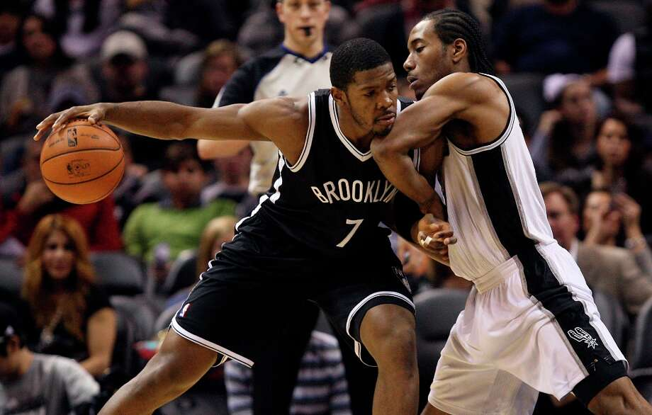 The Nets' Joe Johnson keeps the ball away from the Spurs' Kawhi Leonard during the first half at the AT&T Center, Monday, Dec. 31, 2012. Photo: Jerry Lara, San Antonio Express-News / © 2012 San Antonio Express-News