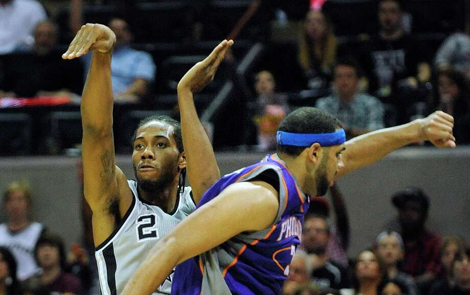 Kawhi Leonard of the Spurs (2) watches as his 3-point shot goes through the hoop as Jared Dudley of the Suns defends at the AT&T Center on Saturday, Jan. 26, 2013. Photo: Billy Calzada, San Antonio Express-News / SAN ANTONIO EXPRESS-NEWS