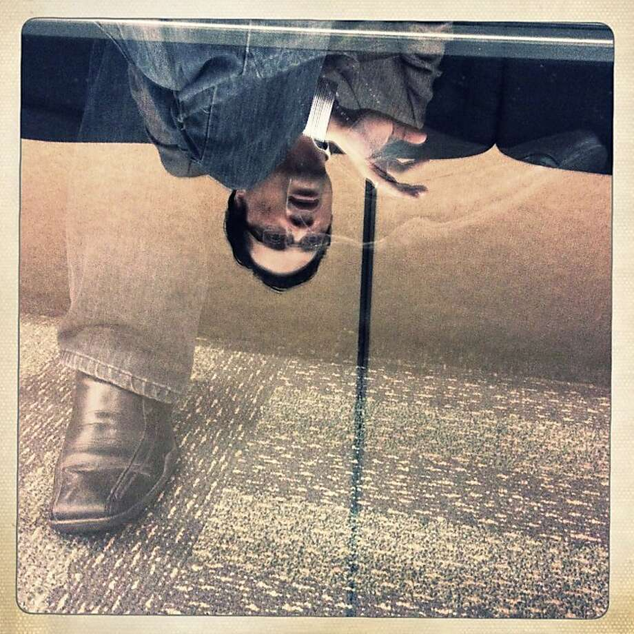 Richard Koci Hernandez, UC Berkeley Graduate School of Journalism assistant professor, is reflected in a glass tabletop in the Media Center after speaking during iPhoneography: The Mobile Masters at Macworld/iWorld in Moscone Center West on Wednesday, January 30, 2013 in San Francisco, Calif. Photo: Lea Suzuki, The Chronicle