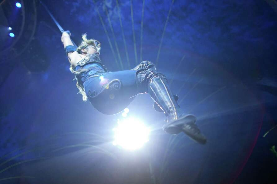 An aerial performer swings high overhead.