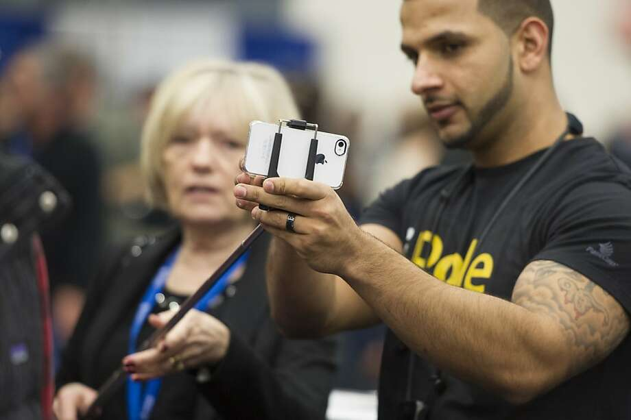 "Attendees try out FastCap Tech's iPole Mini camera pole with an Apple Inc. iPhone at the Macworld/iWorld conference at the Moscone Center West in San Francisco, California, U.S., on Thursday, Jan. 31, 2013. This year's conference, titled ""The Ultimate iFANEvent,"" brings together attendees to celebrate Apple Inc. technology and learn more about products and services for Apple users. Photo: David Paul Morris, Bloomberg"