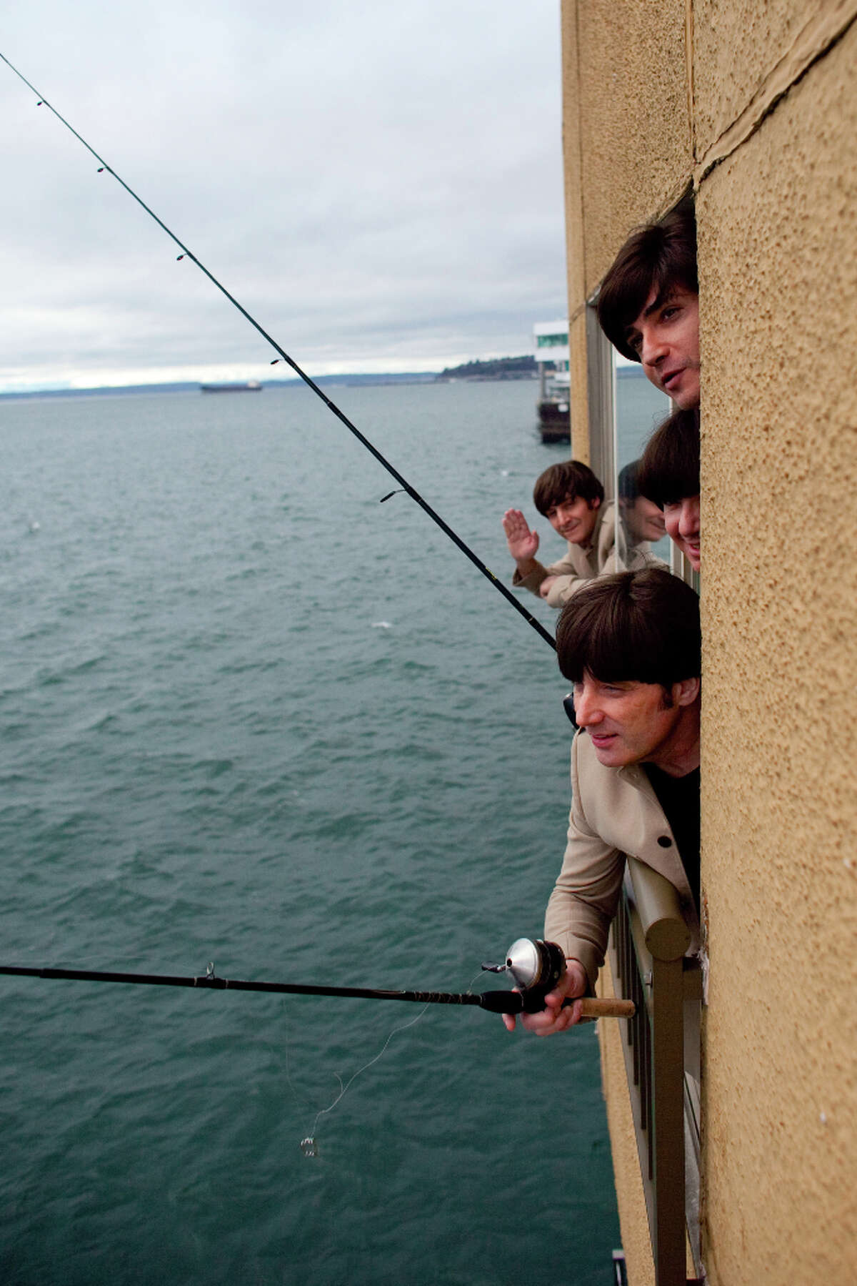 Members of Rain, a Beatles tribute band, reenact an iconic photograph of the Beatles on Thursday, Jan. 31, 2013, at Seattle's Edgewater Hotel. The band, which performed its tribute to the Beatles on Broadway, will be at Seattle's Moore Theatre for shows until Feb. 3.