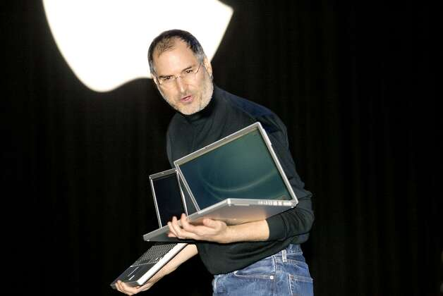 Steve Jobs introduces the new PowerBook at Macworld 2003, claiming it has the biggest screen and smallest size on the market. So why is he using them to do curls? Photo: LIZ HAFALIA, SFC / CHRONICLE