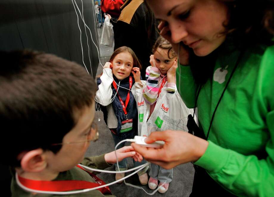 Ben Lancaster, left, and sisters Shelby and Devyn Stasiowski get outfitted for new iPod shuffles at Macworld in 2005. It had a lanyard, which made every adult wearing it look like a child. Photo: Chris Stewart, SFC / The Chronicle