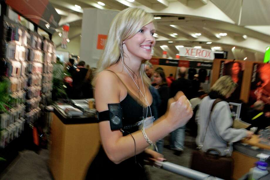 Kelly Vaughn demonstrates an iPod armband at Macworld in 2006. She looks so happy, there's no way that armband ever slips down and yanks the earbuds out like every other iPod armband. Photo: Chris Stewart, SFC / The Chronicle