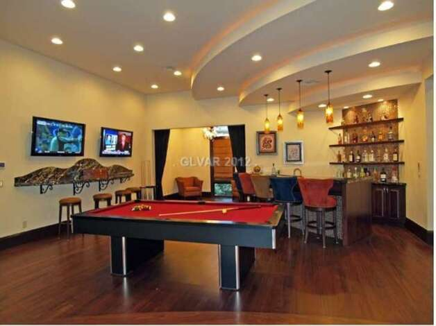 Modern and sleek, this man cave has a full bar with two flat screens and a pool table.  This is part of a Las Vegas home that's listed for $2.99 million.