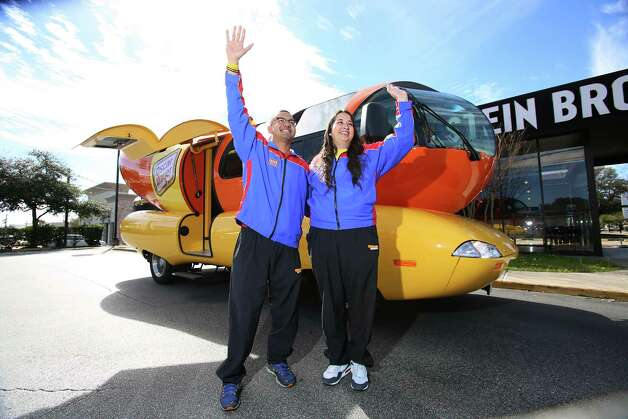 Outside the Oscar Mayer Weinermobile parked on Kirby Thursday, Jan. 31, 2013, Abraham Luna and Emma Cuellar wave to drivers on a mild, partly cloudy day in Houston  Photo: Thomas B. Shea, For The Chronicle / © 2012 Thomas B. Shea