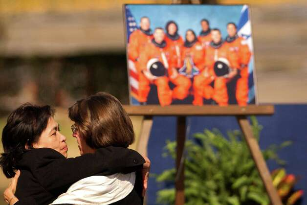 Unidentified crew family members console each other in front of a portrait of the STS-107 crew at the Johnson Space Center during memorial service mourning the loss of the seven astronauts aboard the Space Shuttle Columbia, Tuesday afternoon, February 4, 2002.  (Smiley N. Pool/Chronicle) Photo: SMILEY N. POOL, STAFF / HOUSTON CHRONICLE