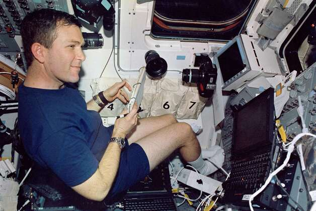 "FILE - In this Jan. 2003 file photo, astronaut Rick D. Husband, mission commander of the space shuttle Columbia, is pictured on the aft flight deck.  Husband and six crew members were lost when Columbia broke up during re-entry over north Texas on Feb. 1, 2003,  This picture was on a roll of unprocessed film recovered by searchers from the debris later, released by NASA on June 24, 2003.  Ten years later, reminders of Columbia are everywhere, including up in the sky.  Everything from asteroids, lunar craters and Martian hills, to schools, parks, streets and even an airport (Rick Husband Amarillo International Airport) bear the Columbia astronauts' names. Two years ago, a museum opened in Hemphill, Texas, where much of the Columbia wreckage rained down, dedicated to ""remembering Columbia.""  About 84,000 pounds of that wreckage, representing 40 percent of NASA's oldest space shuttle, are stored at Kennedy and loaned for engineering research. (AP Photo/NASA) Photo: Anonymous, HOPD / NASA"