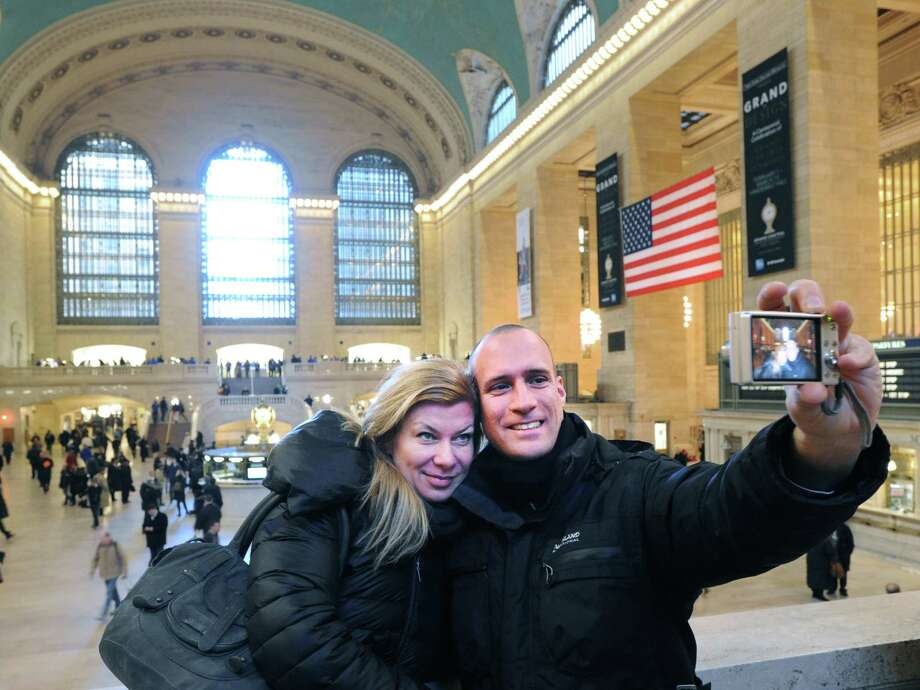 Martin Jezl takes a photo of himself and girlfriend, Ricki Weiss, inside Grand Central Terminal, New York City, Thursday, Jan. 24, 2013. The couple, from Austria, was visiting New York City and wanted to see the landmark terminal that is celebrating its 100th birthday on Febuary 1st. Photo: Bob Luckey / Greenwich Time