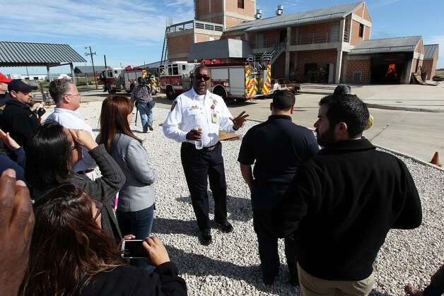 Fire Chief Charles Hood (center) offers details and insights on how firefighters work an active fire scene during a demonstration at the San Antonio Fire Academy for a civilian employee appreciation event on Thursday, Jan. 31, 2013. The employees had an opportunity to see how firefighters worked a fire and took rides in fire trucks including a nearly 90-feet ride in the air in one of the department's aerial platform trucks. Photo: Kin Man Hui, San Antonio Express-News / © 2012 San Antonio Express-News