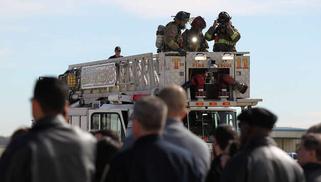 San Antonio firefighters gather onto an aerial platform for a demonstration during a civilian employee appreciation event at the San Antonio Fire Academy on Thursday, Jan. 31, 2013. The employees had an opportunity to see how firefighters worked a fire and took rides in fire trucks including a nearly 90-feet ride in the air in one of the department's aerial platform trucks. Photo: Kin Man Hui, San Antonio Express-News / © 2012 San Antonio Express-News