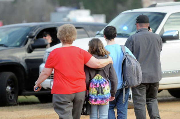 In this Tuesday, Jan. 29, 2013 photo, students and family leave the scene of the school bus shooting. Police, SWAT teams and negotiators were at a rural property where a man was believed to be holed up in a homemade bunker Wednesday, HAN 30, 2013 after fatally shooting the driver of a school bus and fleeing with a 6-year-old child passenger, authorities said. The man boarded the stopped school bus in the town of Midland City on Tuesday afternoon and shot the driver when he refused to let the child off the bus. The bus driver died. Photo: The Dothan Eagle, Danny Tindell