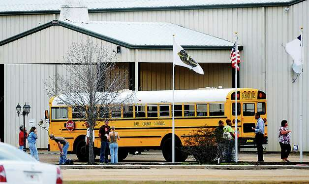 In this Tuesday, Jan 29, 2013 photo, residents look over the school bus where a shooting occurred near Destiny Church along U.S. 231, just north of Midland City, Ala. on Tuesday. Police, SWAT teams and negotiators were at a rural property where a man was believed to be holed up in a homemade bunker Wednesday, HAN 30, 2013 after fatally shooting the driver of a school bus and fleeing with a 6-year-old child passenger, authorities said. The man boarded the stopped school bus in the town of Midland City on Tuesday afternoon and shot the driver when he refused to let the child off the bus. The bus driver died. Photo: The Dothan Eagle, Danny Tindell