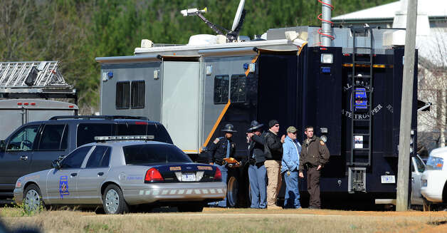 Law officers stand beside the Alabama State trooper mobile command post at the Dale County hostage scene in Midland City, Ala. on Thursday, Jan. 31, 2013. A gunman holed up in a bunker with a 6-year-old hostage has kept law officers at bay since the standoff began when he killed a school bus driver and dragged the boy away, authorities said. Photo: Montgomery Advertiser, Mickey Welsh