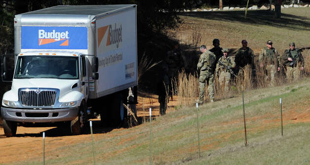 Authorities gather at the Dale County hostage scene in Midland City, Ala. on Thursday morning, Jan. 31, 2013. A gunman holed up in a bunker with a young hostage has kept law officers at bay since the standoff began when he killed a school bus driver and dragged the boy away, authorities said. Photo: Montgomery Advertiser, Mickey Welsh