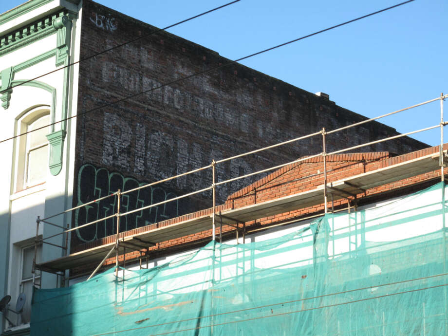 942 Mission and Jessie, early Jan. 2013; Scaffolding goes up on brick building between Alkain and Chronicle hotel, neither noted for deluxe accommodations