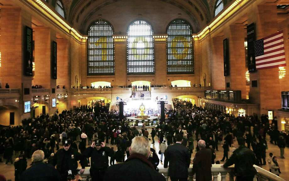 NEW YORK, NY - FEBRUARY 01:  People gather in Grand Central Terminal beneath a '100' sign during centennial celebrations on the day the famed Manhattan transit hub turns 100 years old on February 1, 2013 in New York City. The terminal opened in 1913 and is the world's largest terminal covering 49 acres with 33 miles of track. Each day 700,000 people pass through the terminal where Metro-Noth Railroad operates 700 trains per day. Photo: Mario Tama, Getty Images / 2013 Getty Images