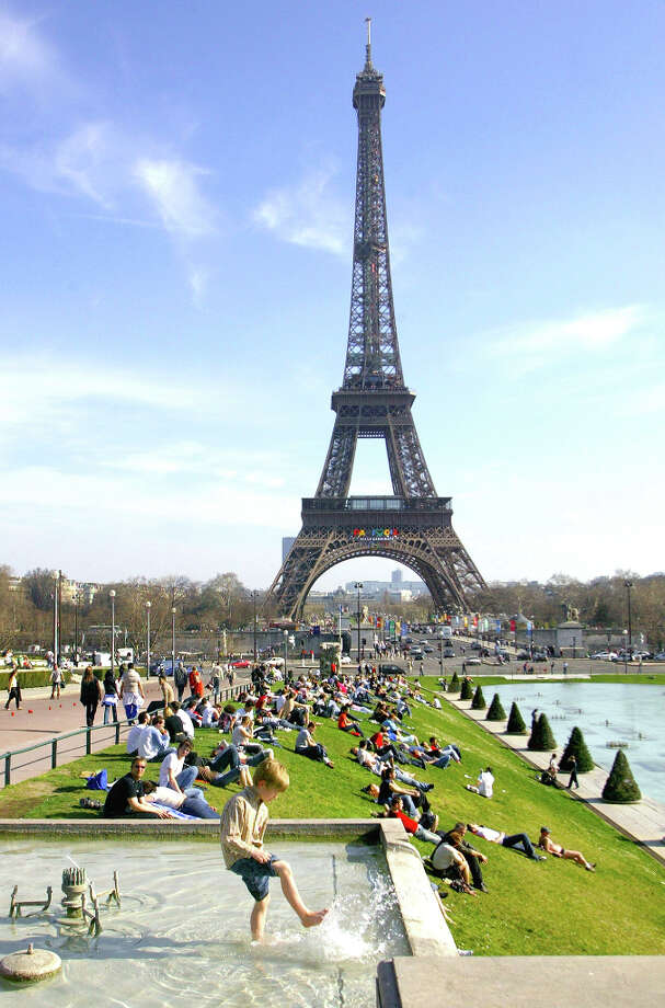 9. PARIS - People relax on the grass as a child paddles in a fountain of the Trocadero gardens, in front of the Eiffel tower in Paris. Photo: FRANCK PREVEL, AP / AP