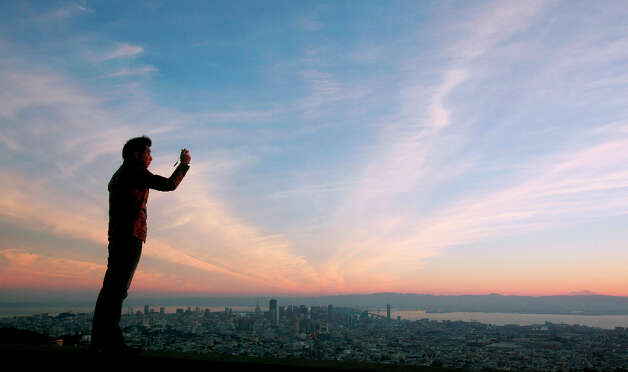 7. SAN FRANCISCO - Yoichi Katayama takes a picture of the sunrise from Twin Peaks in San Francisco. Photo: Jeff Chiu, Associated Press / AP