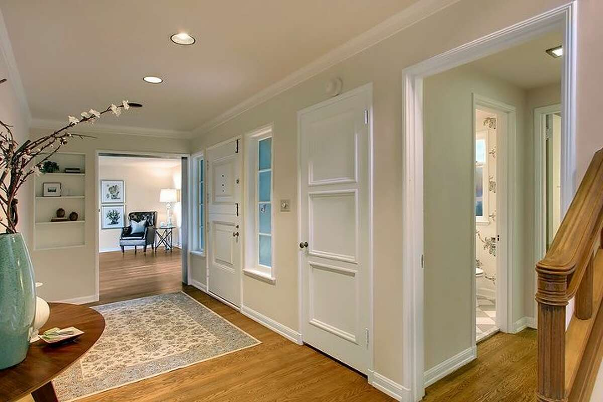 Entry of 1645 E. Boston Terrace. The 3,610-square-foot house, built in 1904, has three bedrooms, 3.5 bathrooms, mahogany-paneled walls in the living room and den, built in shelves, a family room with a vaulted ceiling, a patio, a deck, views of Lake Washington and the Cascade Mountains, and a two-car garage on a terraced, 9,472-square-foot lot. It's listed for $1.295 million.