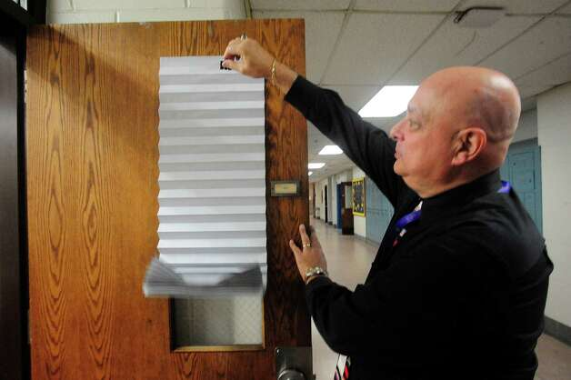 Gary Bocaccio, Danbury High School principal, inspects a new door shade like the ones that will be installed throughout the school soon, during a lockdown drill Friday, Feb. 1, 2013. Photo: Michael Duffy / The News-Times