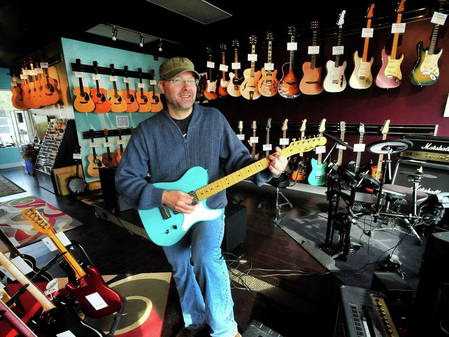 Patrick Nimmo strums a custom-built guitar that's modeled after a Fender Telecaster in his Ridgefield business, Blue Bus Music Friday, Feb. 1, 2013. Photo: Michael Duffy / The News-Times