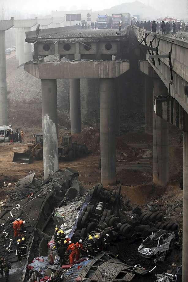 Pyrotechnics cause overpass collapse: Rescuers work among the wreckage of a portion of the Yichang elevated highway that collapsed when a fireworks-laden truck blew up near Sanmenxia, China. The truck was crossing the span when it exploded, causing an 80-meter length to fall and sending other vehicles plummeting to the ground. At least nine people were killed. Photo: Associated Press
