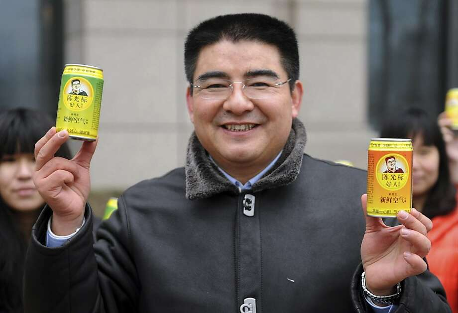 """Now with real oxygen! Your lungs will thank you!Chinese billionaire Chen Guangbiao hawks """"cans of fresh air"""" during a publicity stunt on another day of heavy air pollution in Beijing's financial district. Photo: Associated Press"""