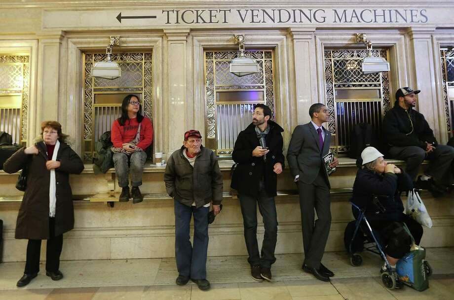 People stand near closed ticket windows in Grand Central Terminal during centennial celebrations. The terminal opened in 1913 and is the world's largest terminal covering 49 acres with 33 miles of track. Each day 700,000 people pass through the terminal where Metro-Noth Railroad operates 700 trains per day. Photo: Mario Tama, Getty Images / 2013 Getty Images