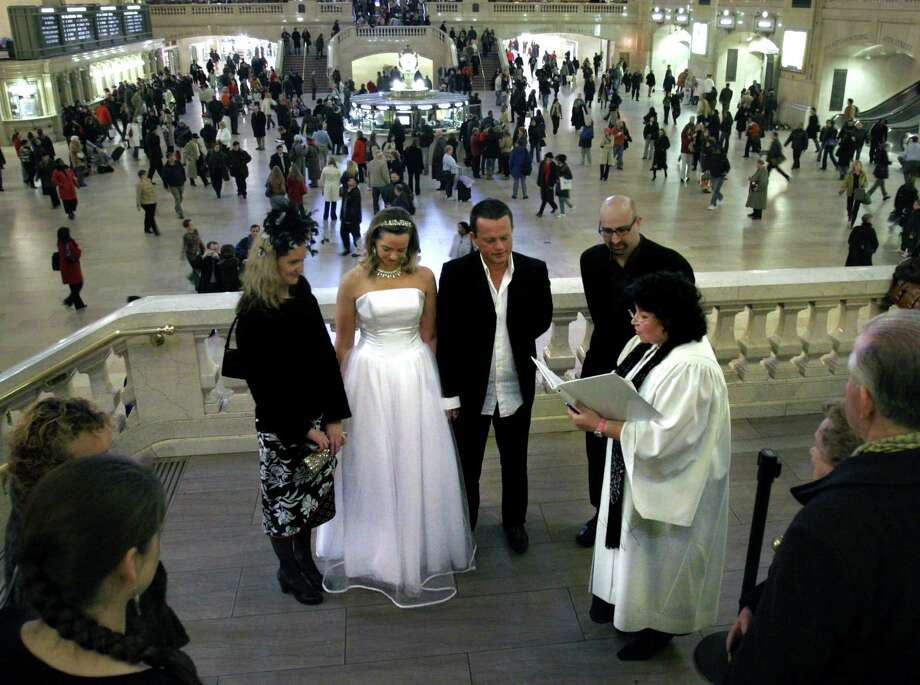 Rev. Laurie Sue, far right, officiates the marriage ceremony for Jackie Forster, second from left, from London, England, and Rob Casserly, center, from Dublin, Ireland, in  Grand Central Station in New York, Friday Dec. 2, 2005. Casserly says having a public wedding at Grand Central was his statement against terrorism post 9/11. Photo: BEBETO MATTHEWS, AP / AP