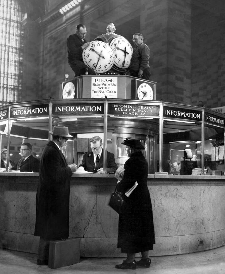 Workers reinstall the clock at the information booth at Grand Central Terminal, in New York, March 4, 1954. Grand Central Terminal was the dream of an engineer whose vision helped shape New York City and modern imagination. Photo: NEAL BOENZI, New York Times / The New York Times  Associated Press