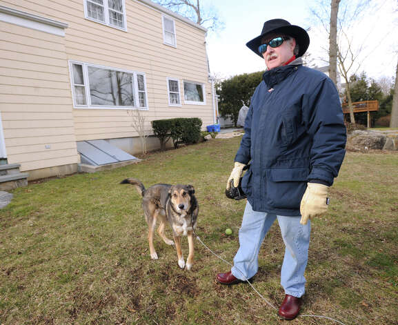 Christopher Semmes with his dog Storm at his Pilgrim Drive home in western Greenwich, Friday, Feb. 1, 2013. Semmes says he has spotted a sickly looking coyote near his home recently and is concerned for the safety of his family and his dog, which spends time outside. Photo: Bob Luckey / Greenwich Time