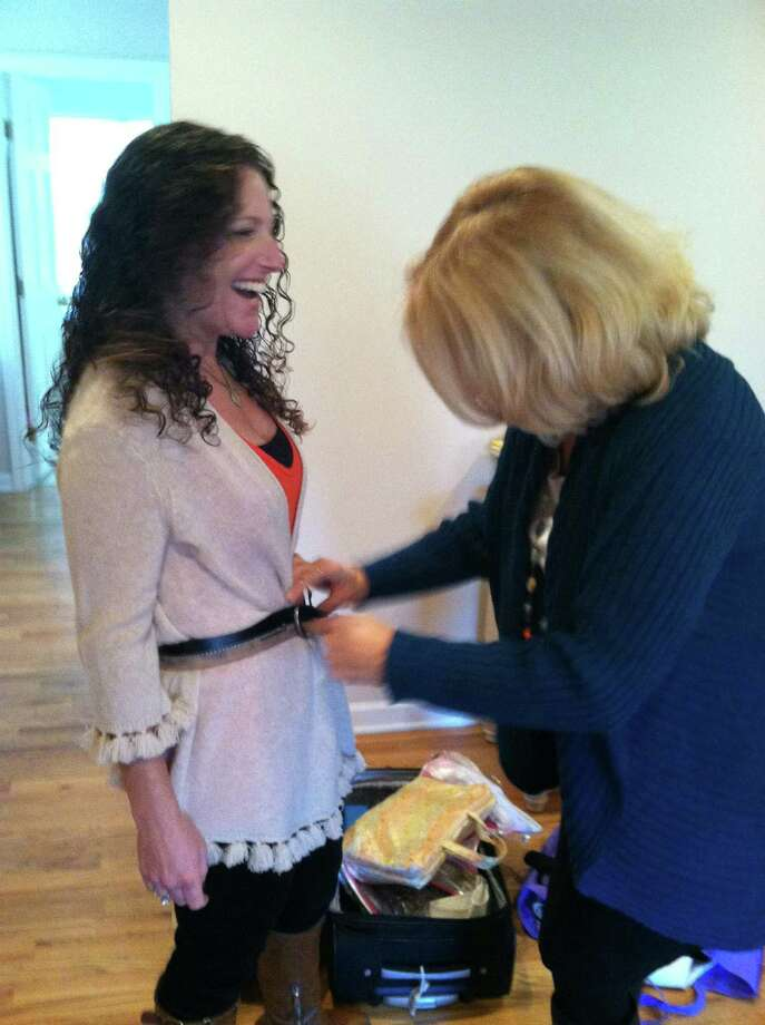 HealthyLife cover model Tara Cook-Littman laughs as wardrobe consultant Pamela Friedlander tightens her belt while putting together potential outfits for Cook-Littman to wear during the magazine's cover shoot. Photo: Rebecca Haynes / HealthyLife