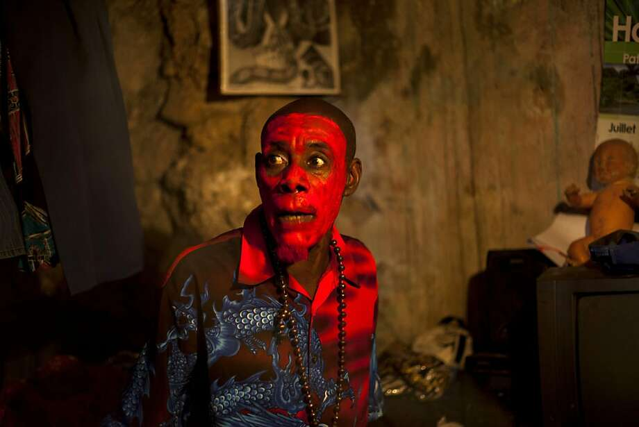 A snake handler Saintilus Resilus, with his face painted red, talks to his assistants as they get ready to perform during pre-Lenten Carnival season in Petionville, Haiti. Resilus sees himself as something of a performance artist, showing off with snakes and other animals that Haitians don't see every day, earning tips from impromptu audiences.  Photo: Dieu Nalio Chery, Associated Press