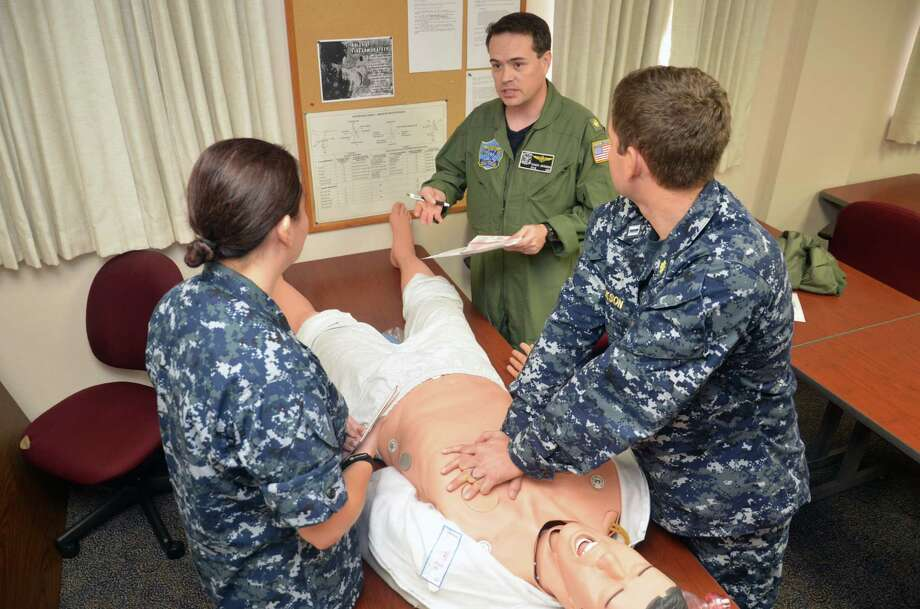 Naval Aerospace Medical Institute (NAMI) flight surgeon Lt. Cmdr. Charles Johnson, center, provides student flight surgeons Lt. Jennifer Hunt, left, and Lt. John Jackson feedback during an Advanced Cardiovascular Life Support block of instruction at NAMI in Pensacola, Fla. The ACLS is an American Heart Association-credentialed course which Navy Medicine deployers are required to take. Photo: Bruce Cummins, U.S. Navy Photographer