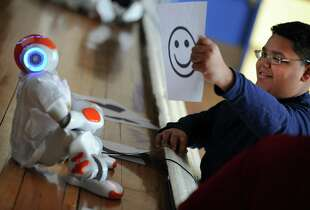 "Sixth grade student Izaiha Mellow-Valle holds up a smiley face for ""Quiz,"" a two-foot tall robot, during its visit to Beardsley School in Bridgeport, Conn. Friday Feb. 1, 2013.  The star of a Robot Humanoid exhibit at Hartford's Connecticut Science Center, Quiz got his name through a contest held in cooperation with Hearst Newspapers that drew more than 200 entries. Lisette Valle, Izaiha's mom, a librarian at Park City Magnet School won the contest. She said she chose the name because the science center is the perfect place for inquisitive minds. Her prize included a one-year, four-person Science Center membership package and the ability to send the robot out for an educational session at a classroom of her choice."