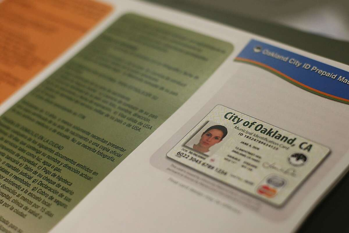 A sample of the Oakland municipal identification card is displayed on a brochure. The municipal identification doubles as a debit card and is aimed at undocumented immigrants as well as people who wish to not have their gender on the card.