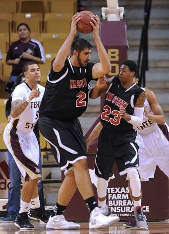 New Mexico State center Sim Bhullar grabs a rebound as teammate Daniel Mullings (23) and Corey Stern of Texas State watch during action in San Marcos on Thursday, Jan. 31, 2013. Photo: Billy Calzada, Express-News / San Antonio Express-News