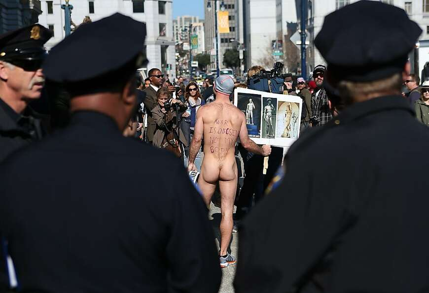 Nude activist Trey Allen holds up pictures of nude statues as he protests San Francisco's new ban on